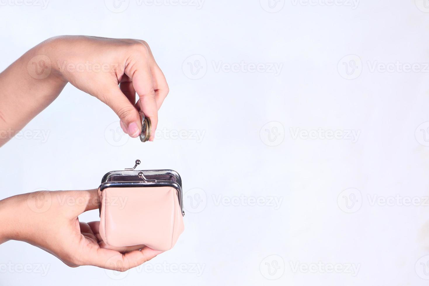 sätta mynt i en myntväska på vit bakgrund foto
