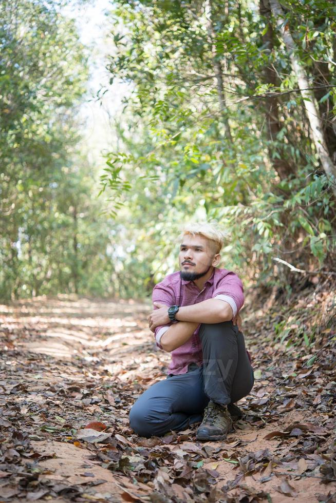 aktiv ung man vandrare tar vila med naturen efter att ha gått genom skogen foto
