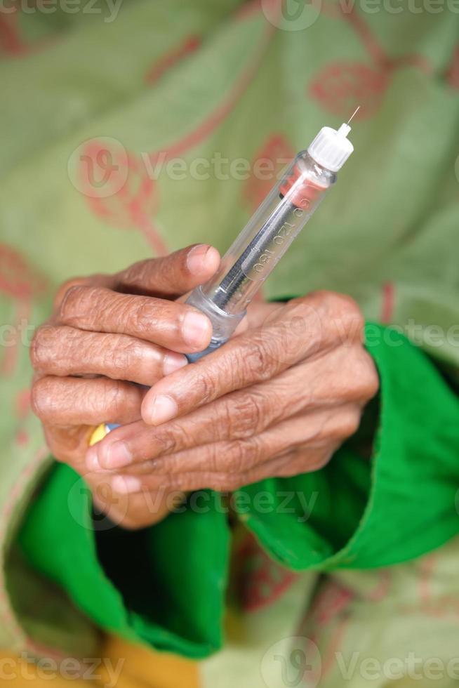 kvinna som håller insulinpenna foto