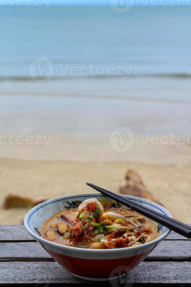 kryddig tom yum soppa på stranden foto