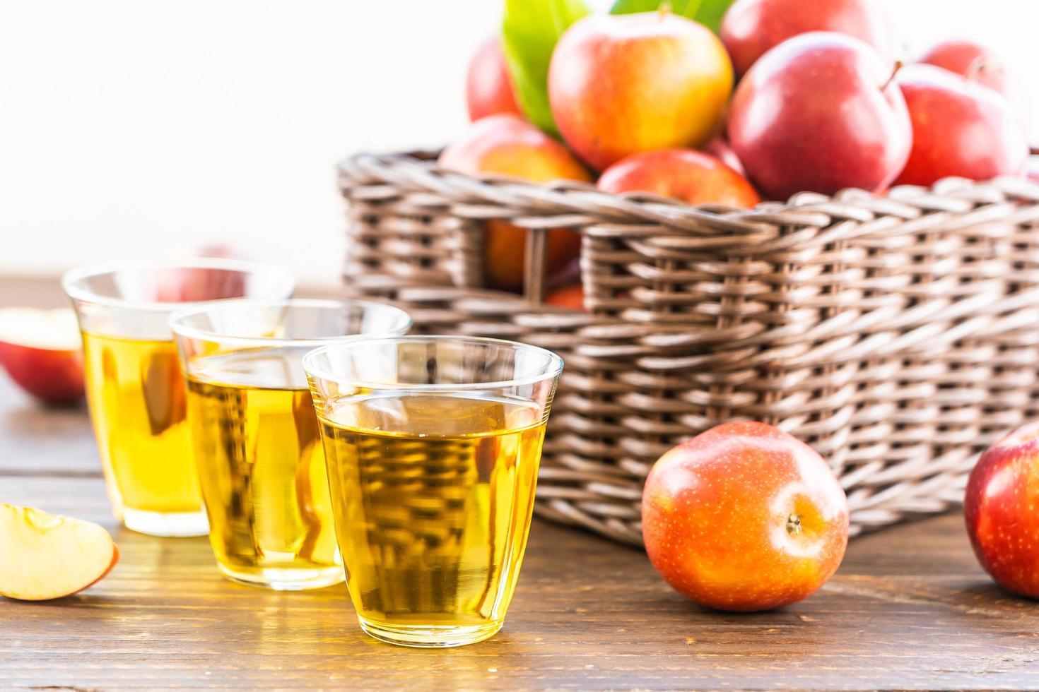 äppeljuice i glas och äpplen i korgen foto