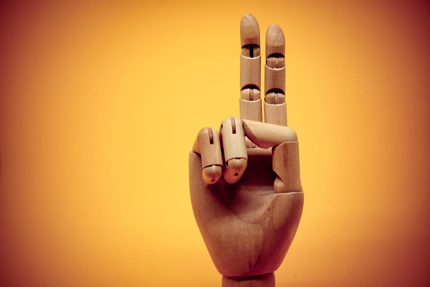 trähand som pekar uppåt två fingrar foto