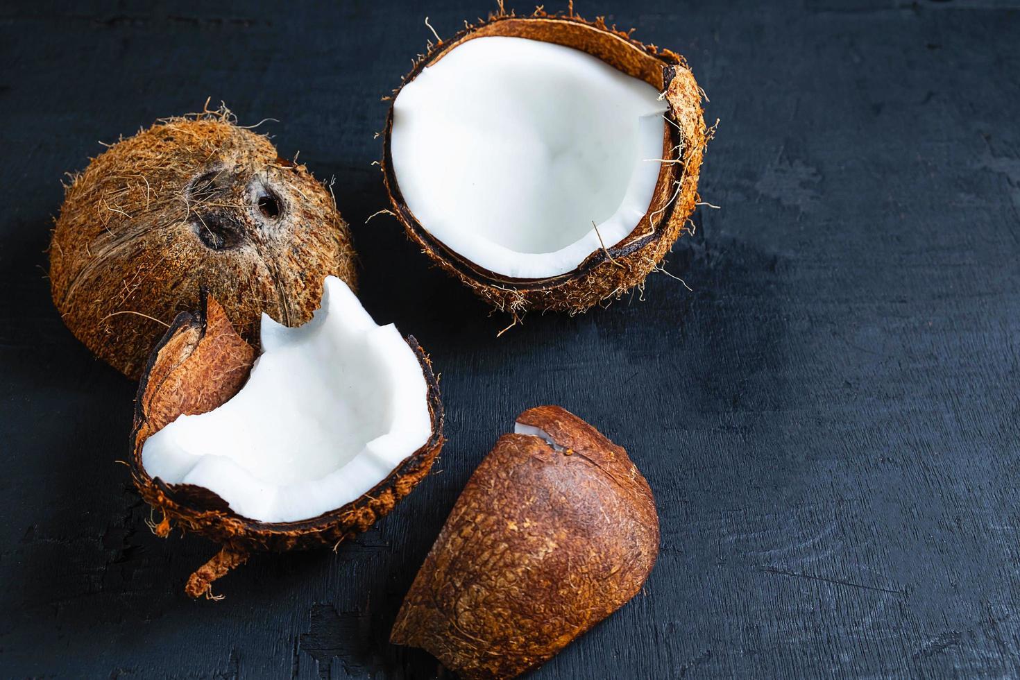 kokosnöt halverad på en svart bordsbakgrund foto