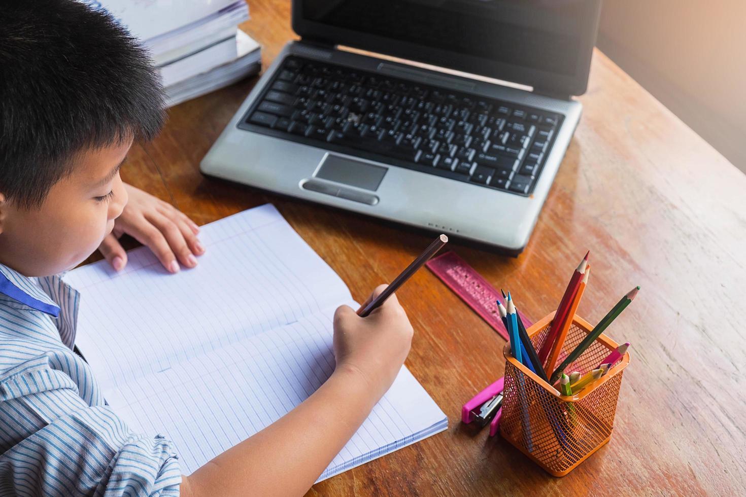 pojke gör läxor med anteckningsboken, bärbar dator, häftapparat och en kopp pennor på ett träskrivbord foto