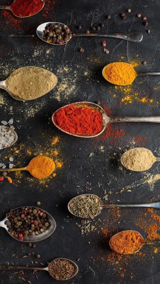 ovanifrån av kryddor i skedar på en mörk bakgrund foto