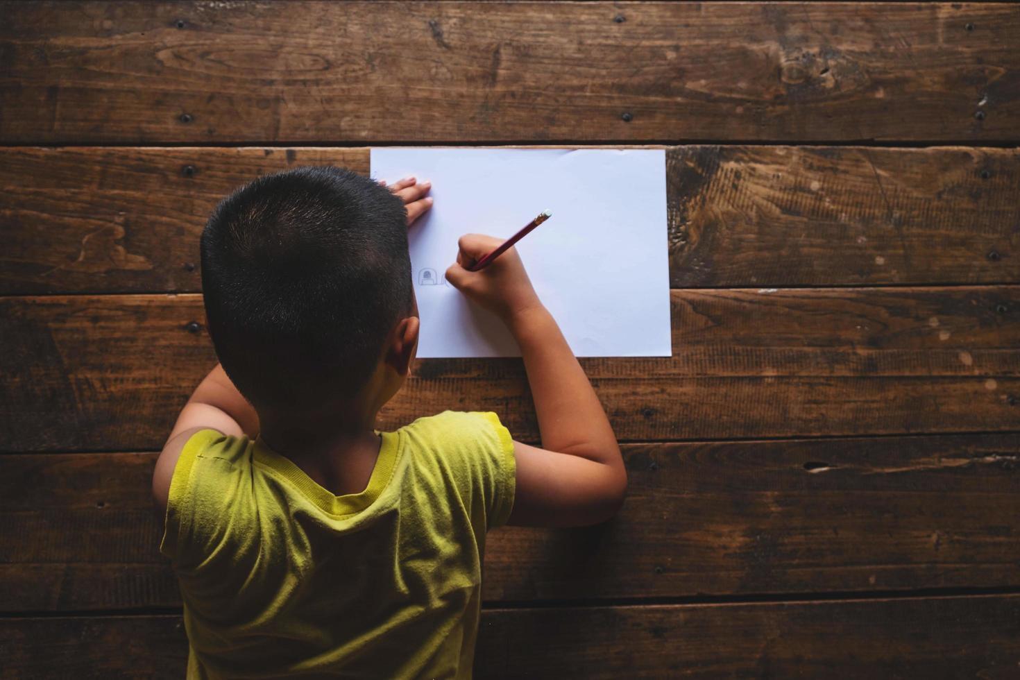 pojke sett bakifrån skriver på papper på trägolv foto