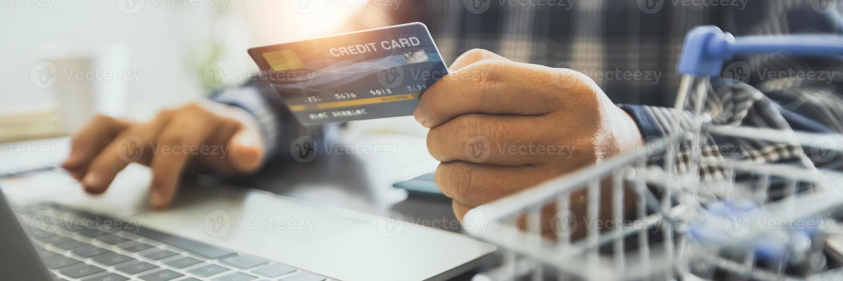 man som håller kreditkortet och arbetar på en bärbar dator foto