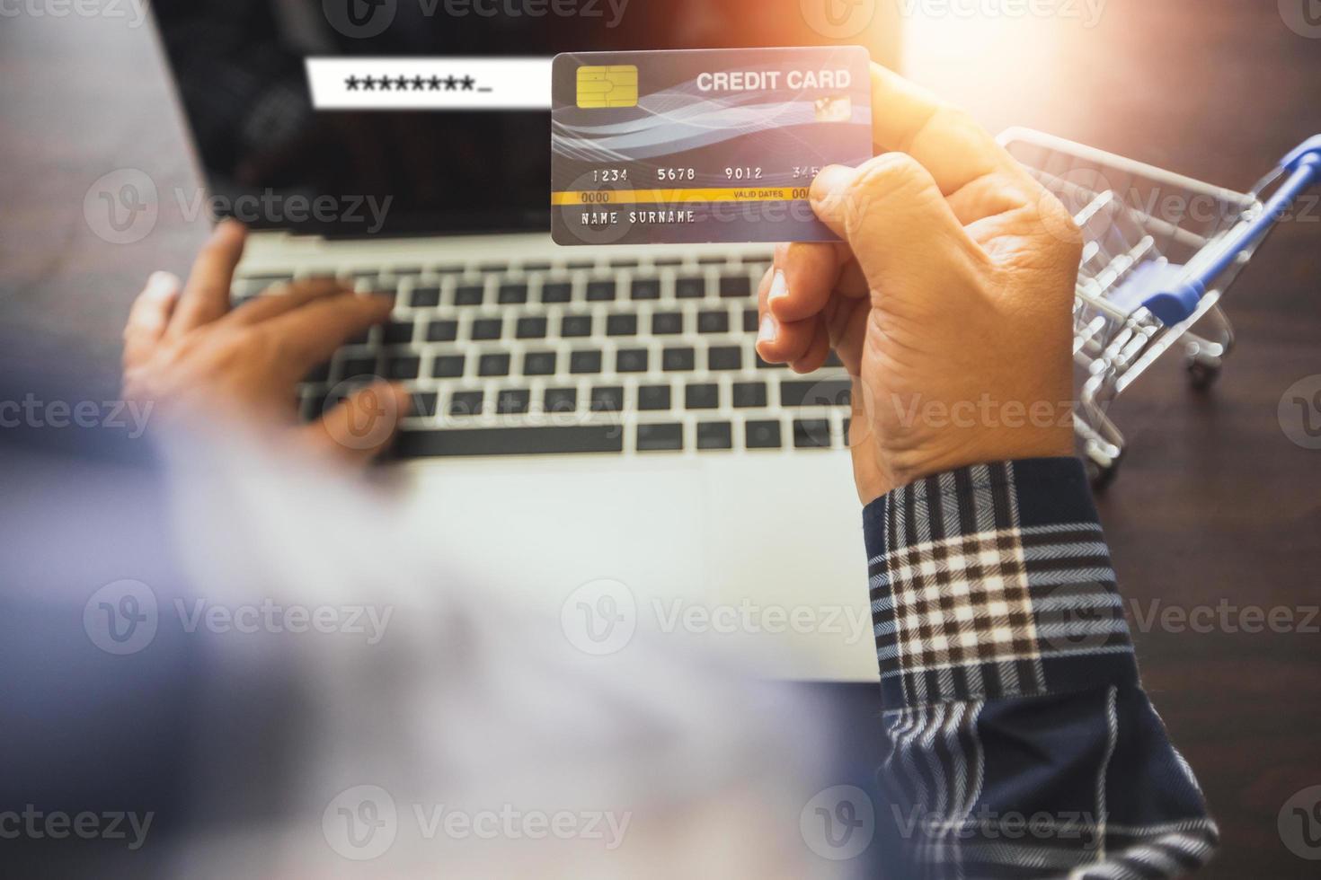 närbild hand av mannen håller kreditkort och arbetar på bärbar dator bredvid miniatyr kundvagn foto