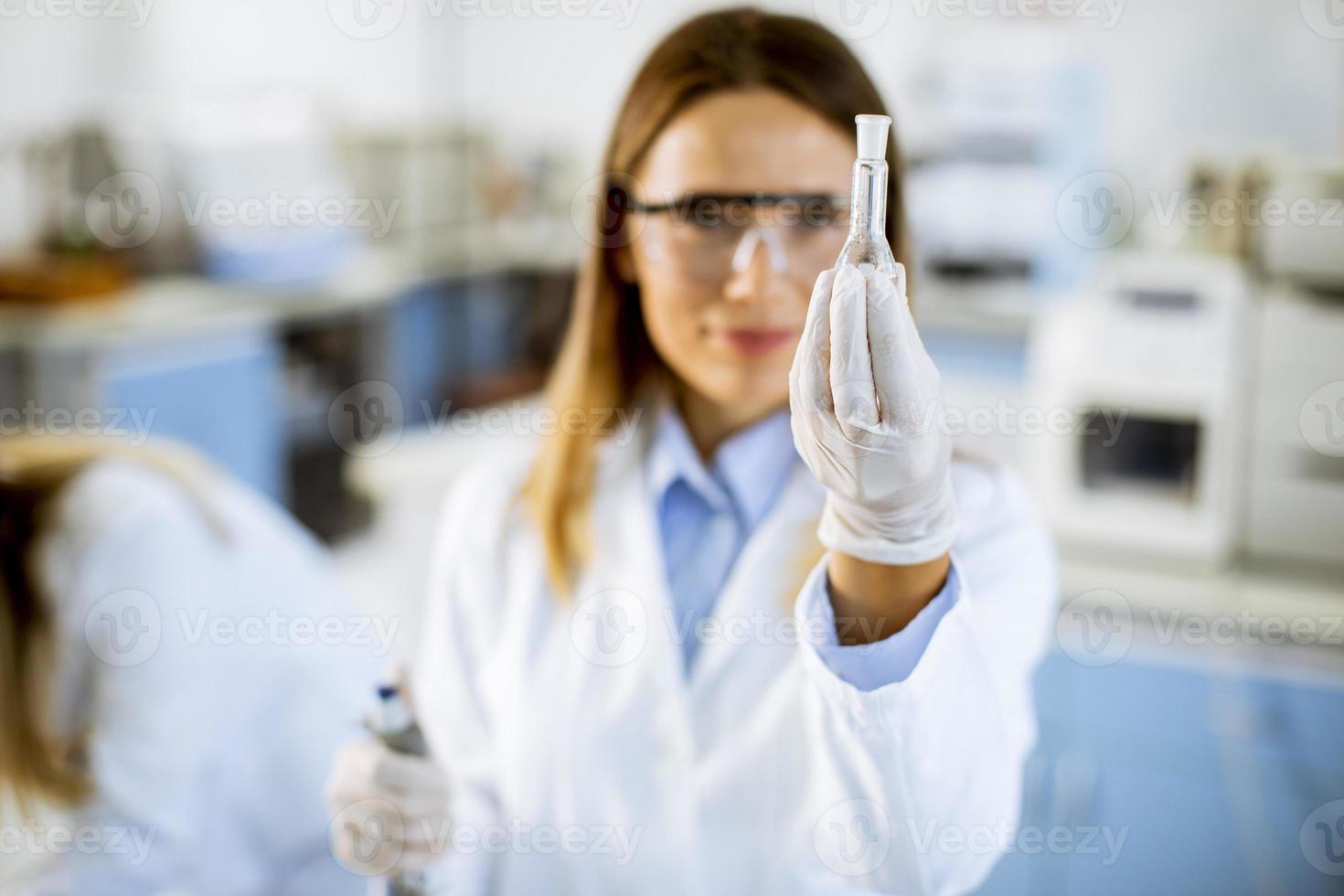 kvinnlig läkare som bär skyddande ansiktsmask i laboratoriekolv med flytande prov foto