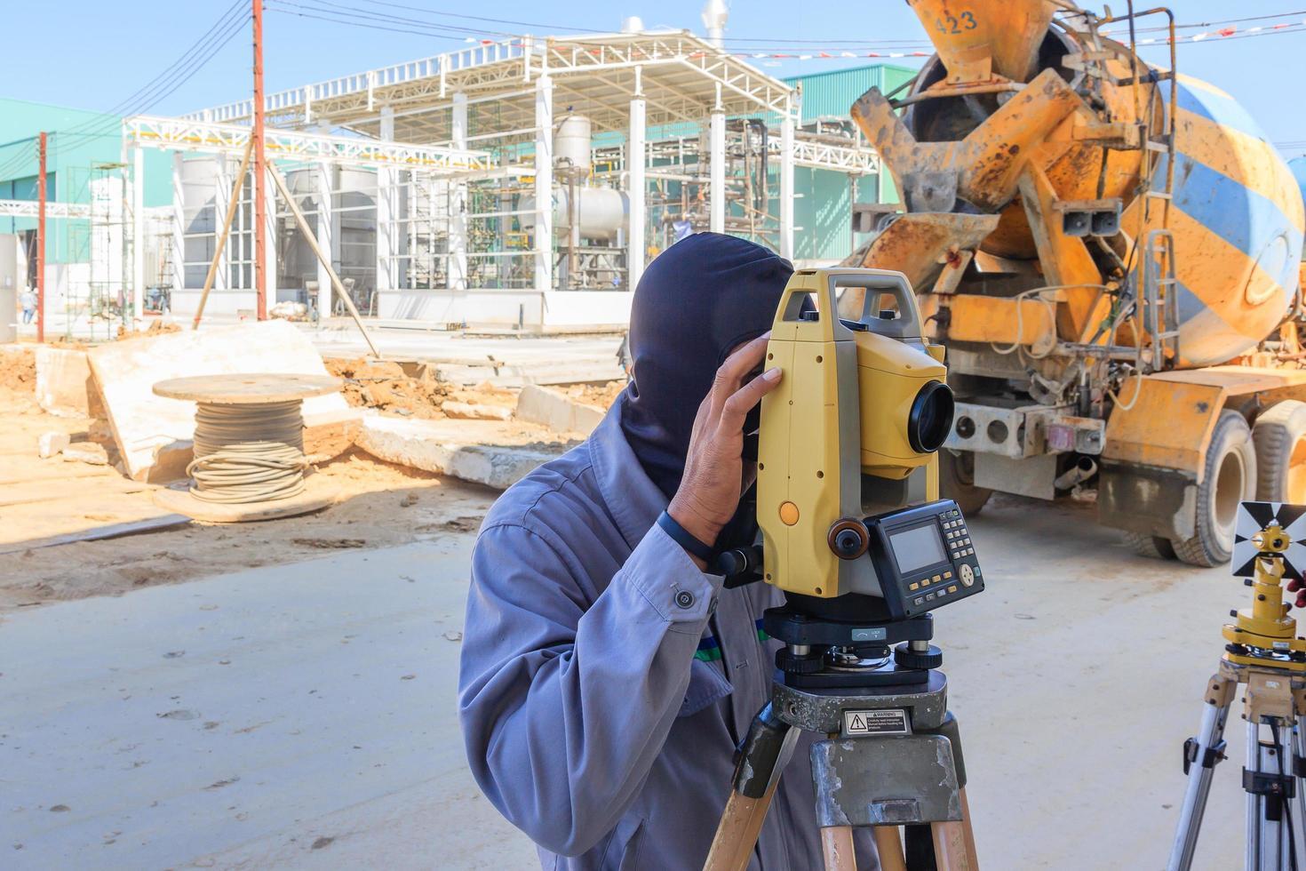 mätare som gör mätning med teodolitutrustning på byggarbetsplatsen. foto