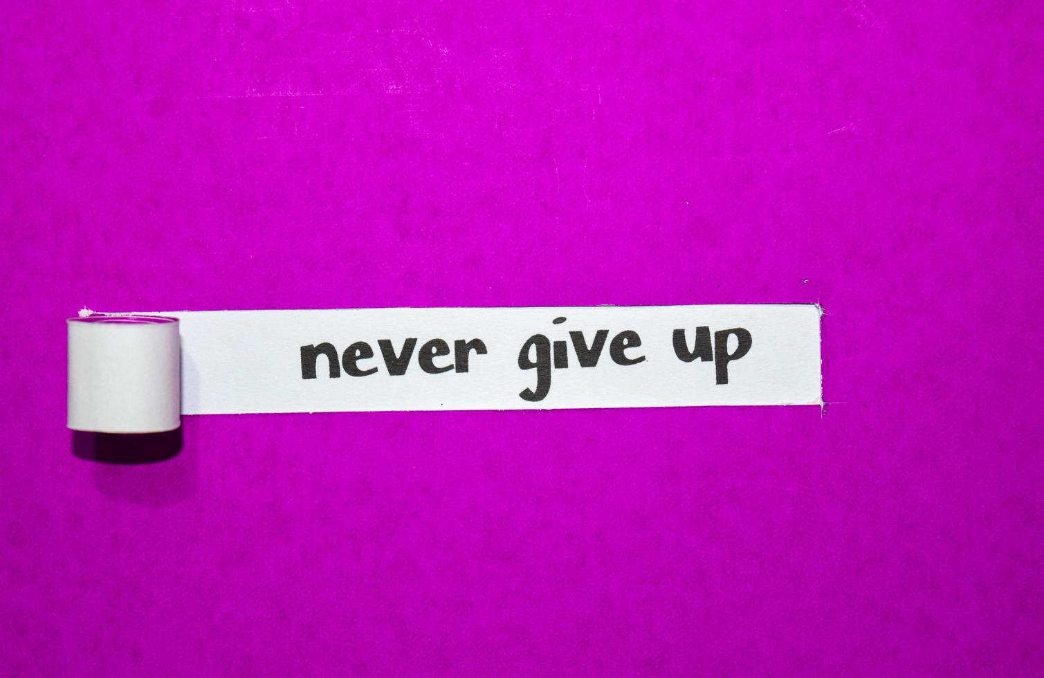 ge aldrig upp text, inspiration, motivation och affärsidé på lila sönderrivet papper foto