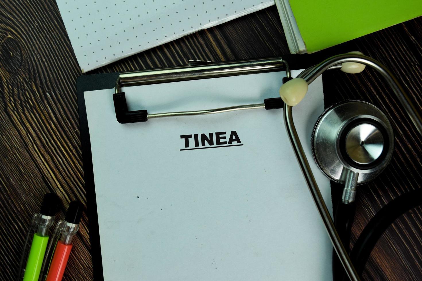 tinea skriven på pappersarbete isolerad på träbord foto