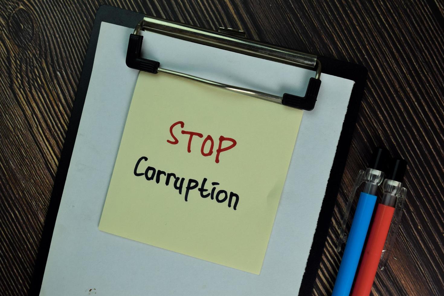stoppa korruption skriven på fästis isolerad på träbord foto