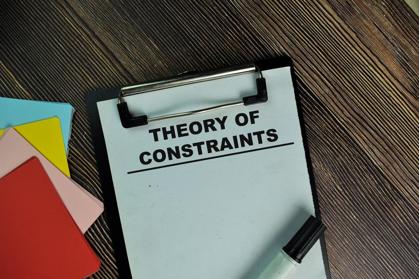 teori om begränsningar skrivna på pappersarbete isolerad på träbord foto