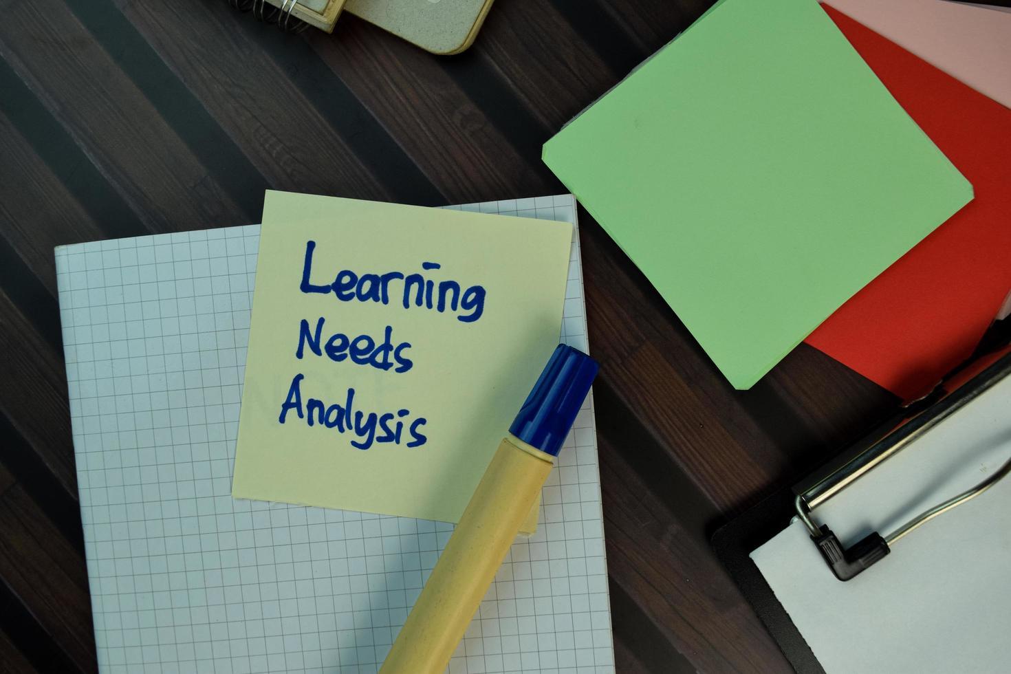 inlärningsbehovsanalys skriven på fästis isolerad på träbord foto