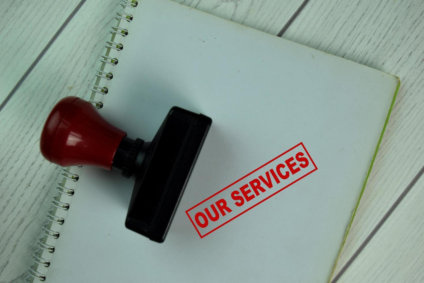 rött handtag gummi stamper och våra tjänster text isolerad på bordet foto