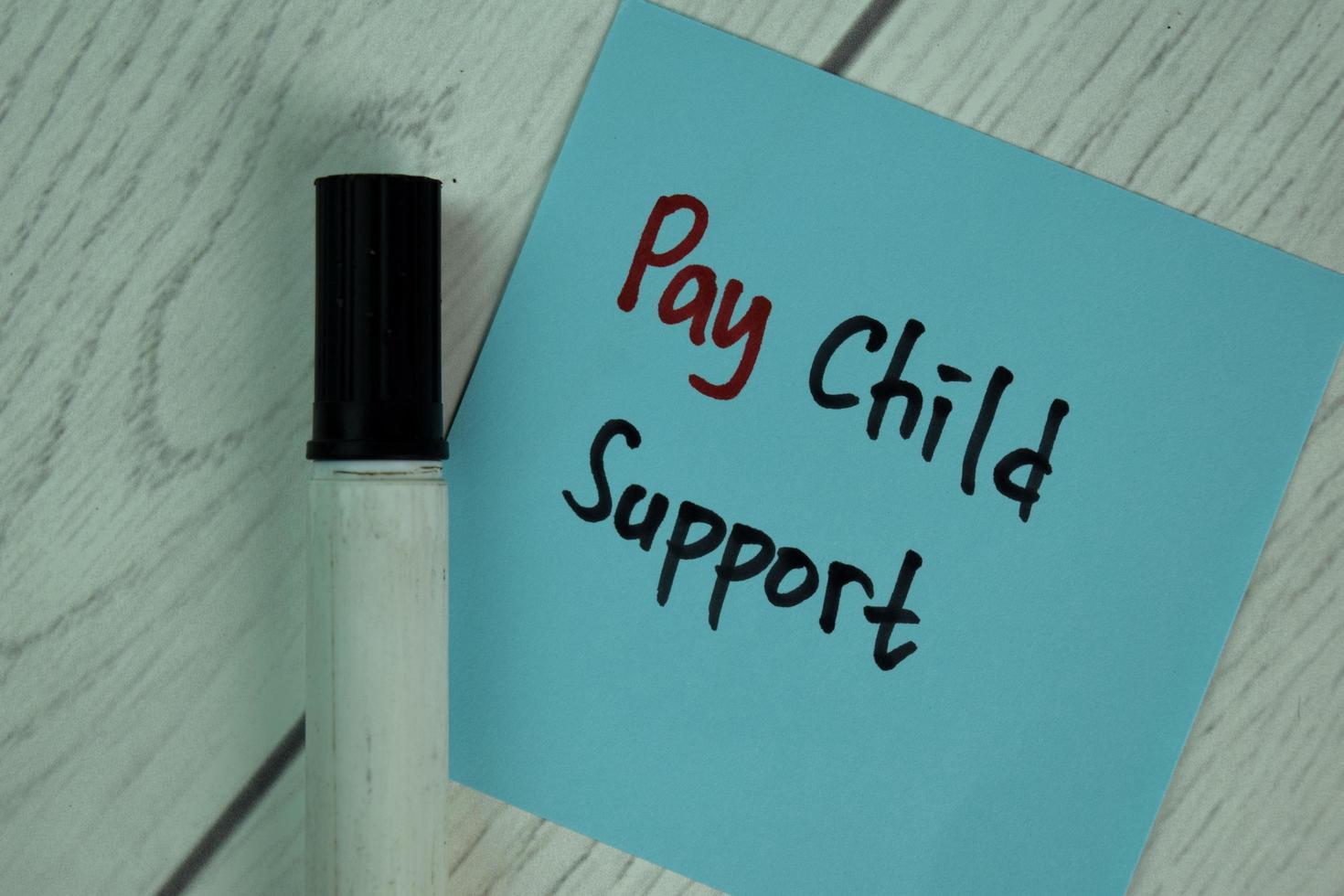 betala barnbidrag skrivet på fästis isolerad på träbord foto