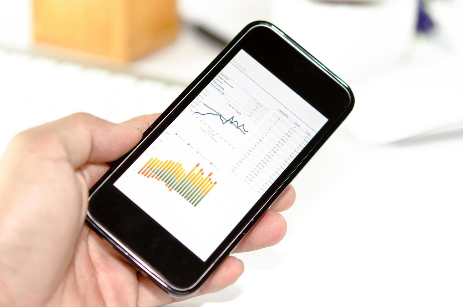 grafer på en smartphone i handen foto