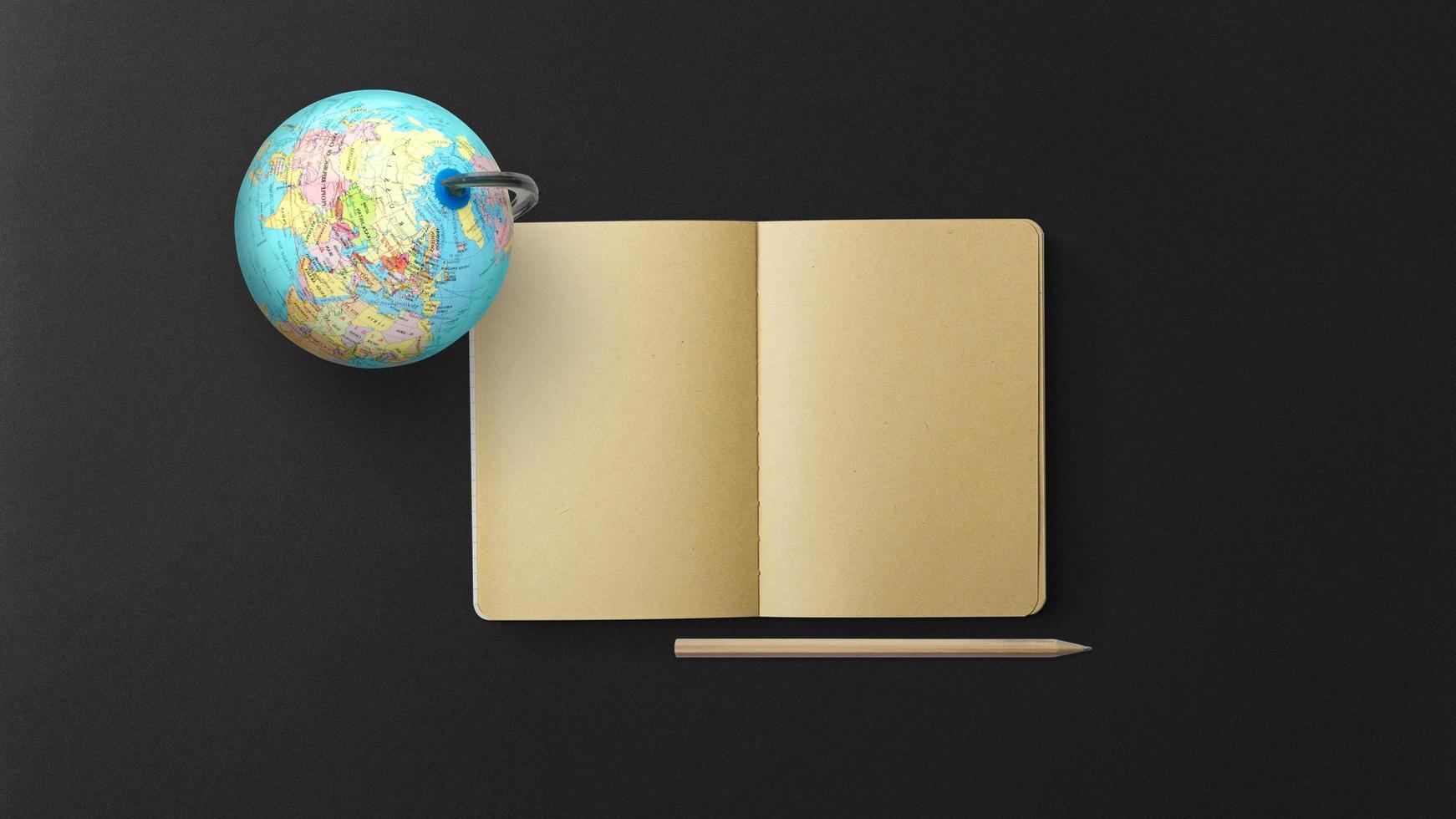 jordglob med anteckningsbok och penna på svart bakgrund foto