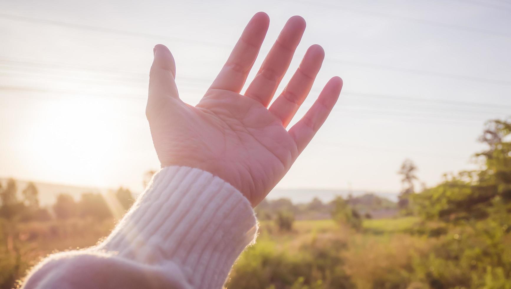 mjukt fokus på kvinnans hand som når mot naturen och himlen foto