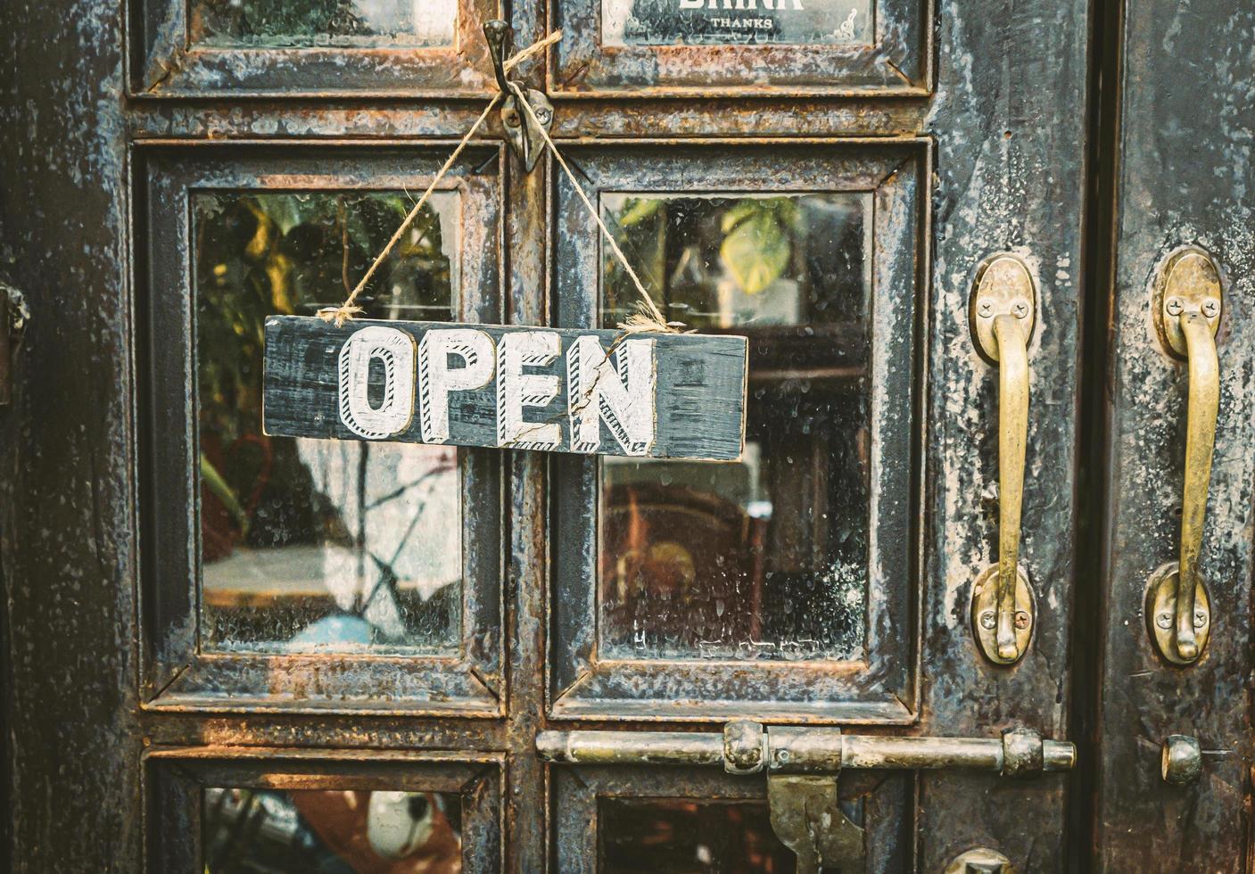 öppet skylt hängande på vintage dörr foto