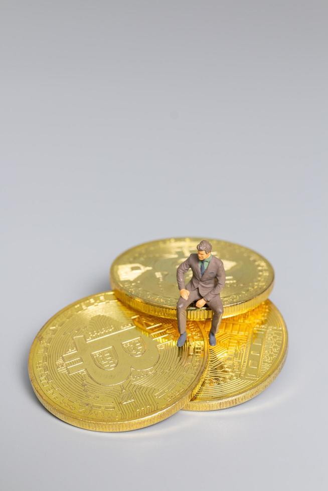 miniatyr affärsman sitter på bitcoin mynt, framtida investering koncept foto