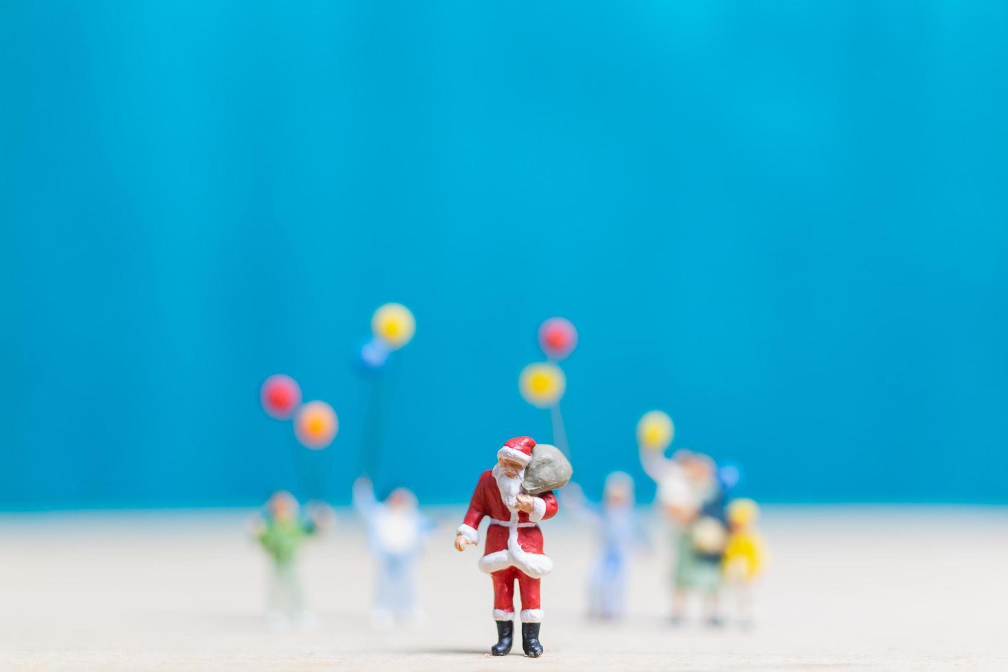 miniatyr Santa Claus och barn som rymmer ballonger, god jul och gott nytt år koncept foto