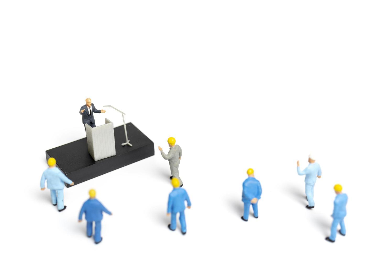 miniatyrfolk som lyssnar på en politiker som talar under ett valmöte foto