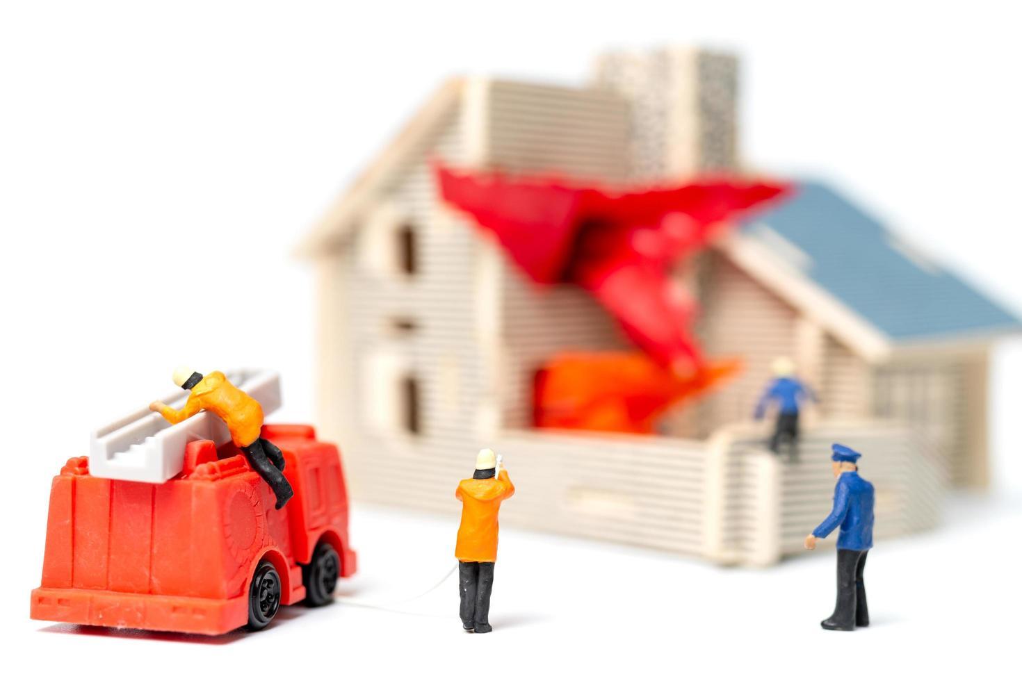 miniatyr brandmän tar hand om en brand nödsituation vid ett trähus foto