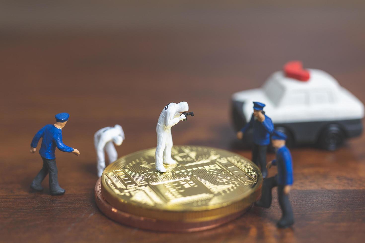 miniatyrpolis och detektiver som står framför bitcoin-kryptokurrency, cyberbrottskoncept foto