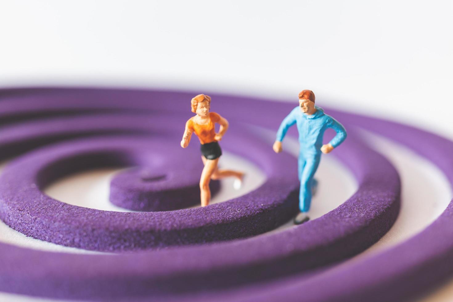 miniatyrpar som kör på ett lila cirkulärt fält foto