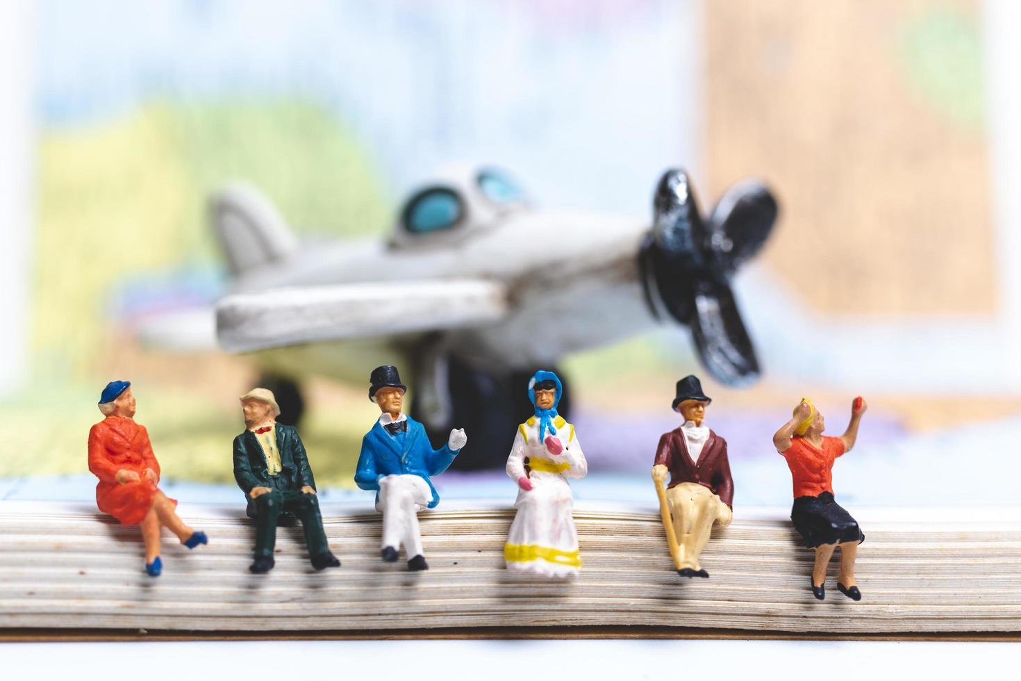 miniatyr människor som sitter på flygplanet med världskarta bakgrund foto