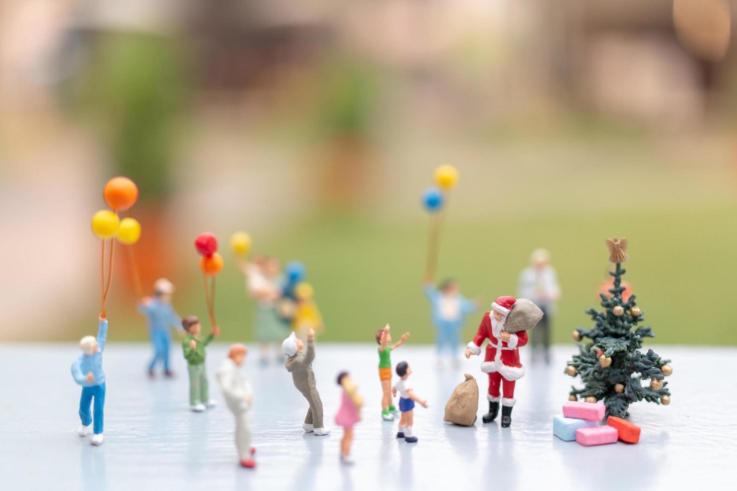 miniatyr Santa Claus håller gåvor för en lycklig familj, jul och gott nytt år koncept foto
