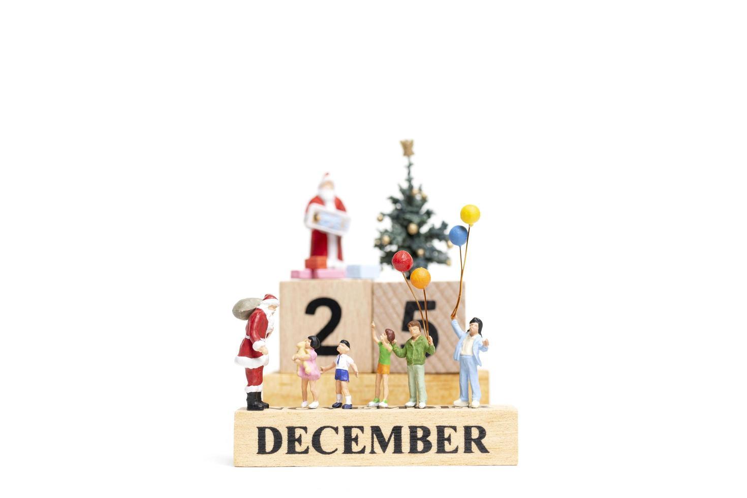 miniatyr jultomten håller gåvor för en lycklig familj med datumet 25 december på en vit bakgrund foto