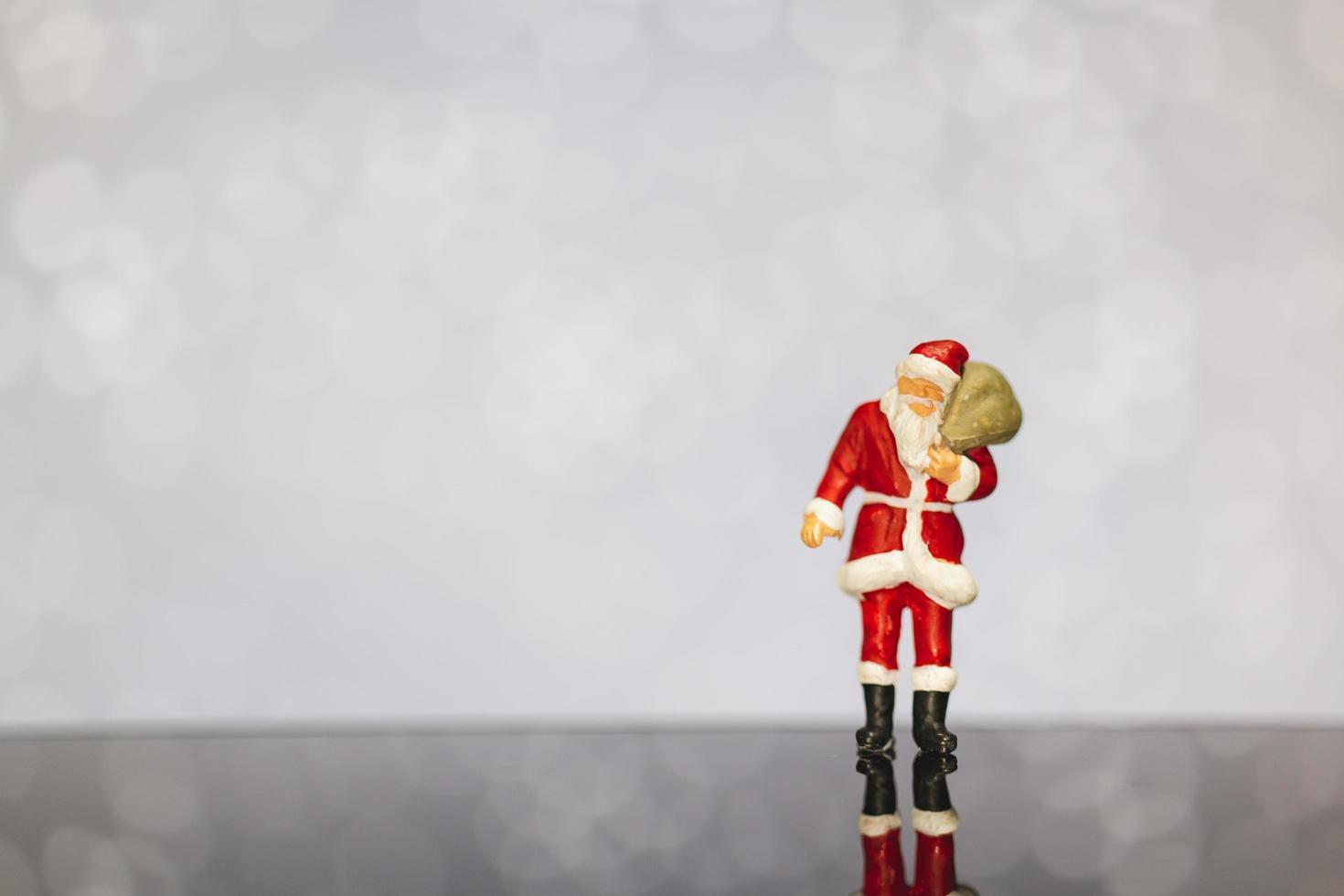 miniatyr jultomten bär en påse på en bokeh bakgrund, god jul och gott nytt år koncept. foto