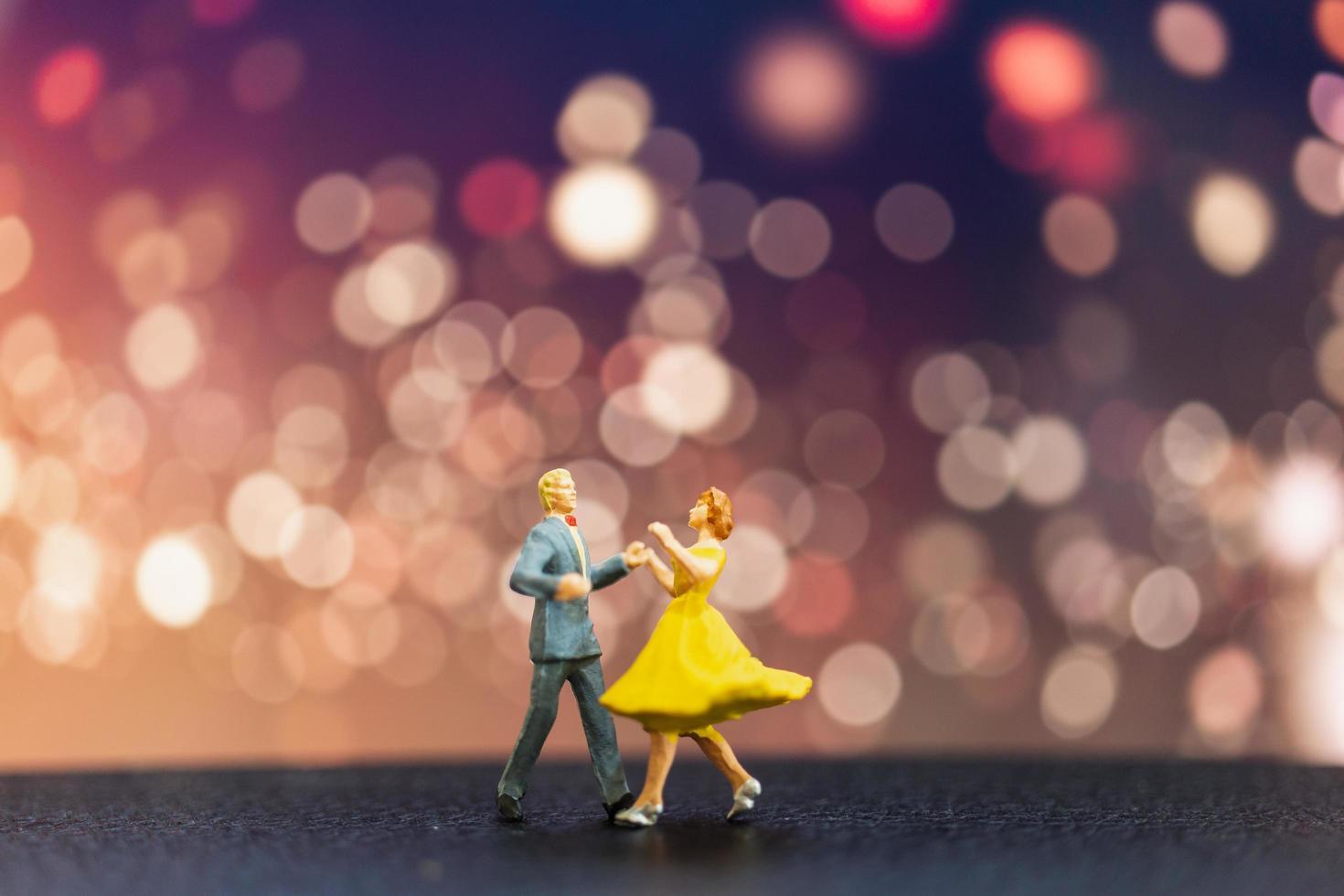 miniatyrpar som dansar med bokehbakgrund, alla hjärtans dagskoncept foto