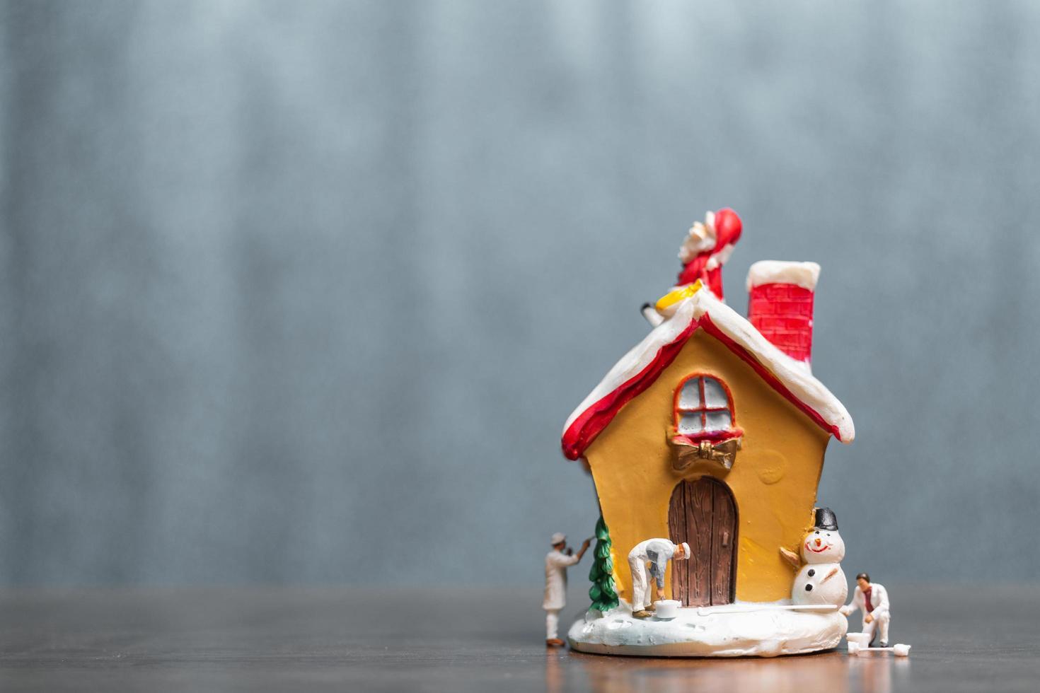 miniatyrfolk som målar ett hus och jultomten som sitter på taket, god jul och lycklig helgkoncept foto