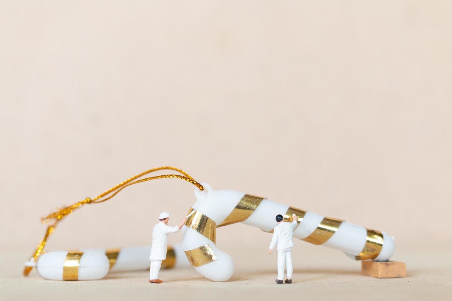 miniatyrarbetare som samarbetar för att måla en juldekoration, jul och gott nytt årskoncept foto