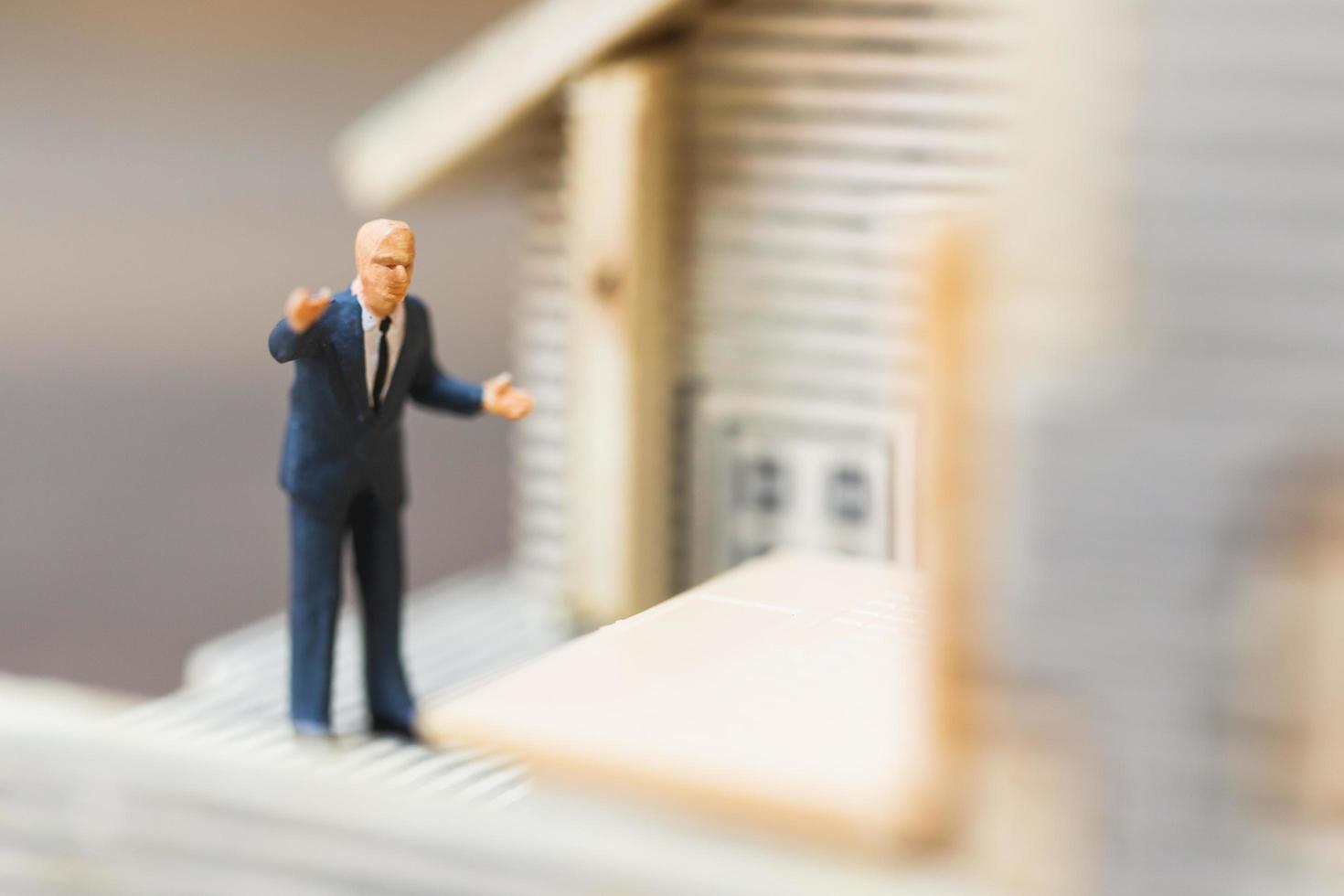 miniatyr affärsman som arbetar med en bärbar dator, koncept för arbete hemma foto