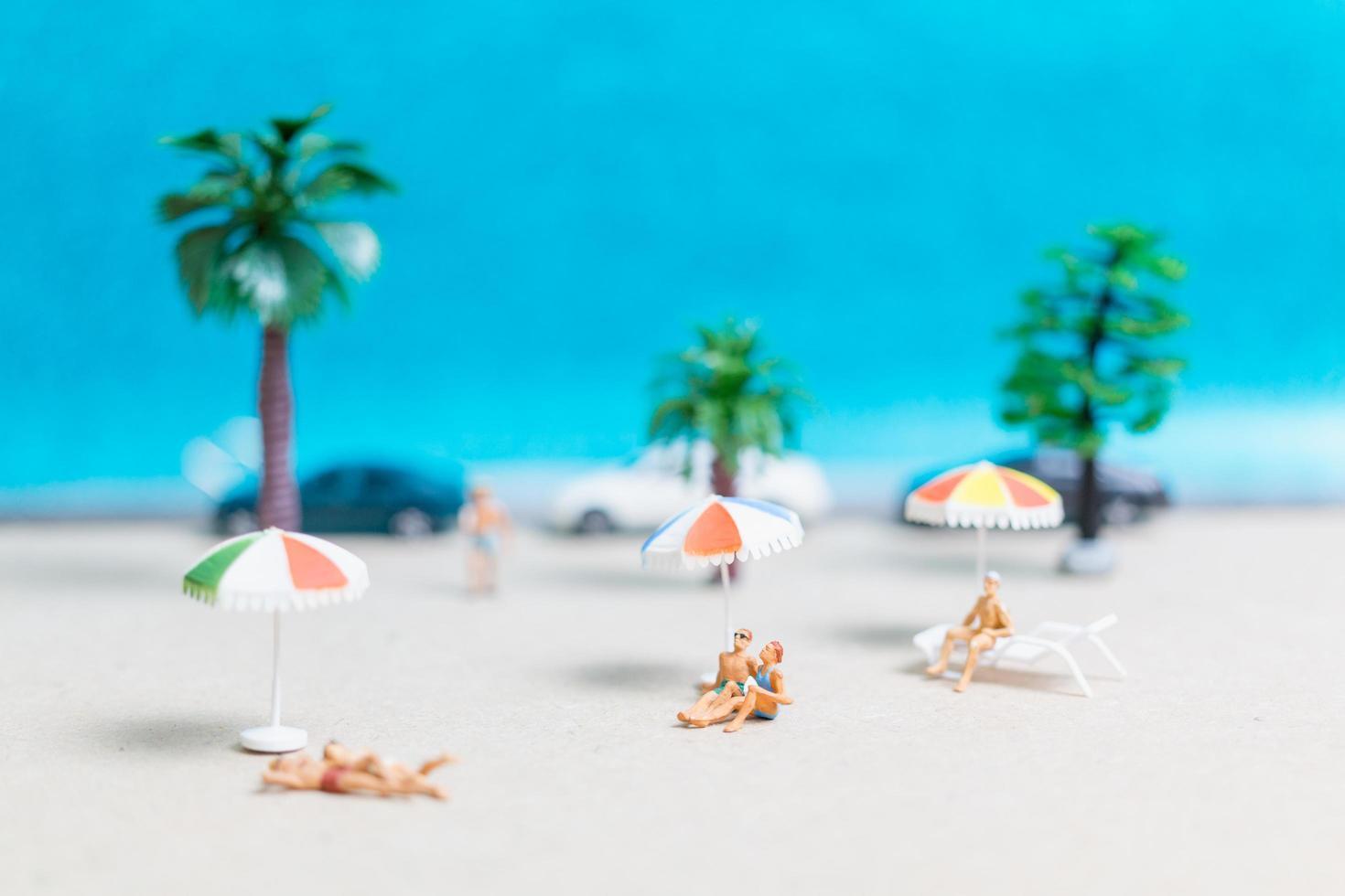 miniatyrfolk som bär baddräkter som kopplar av på en strand med en blå bakgrund foto