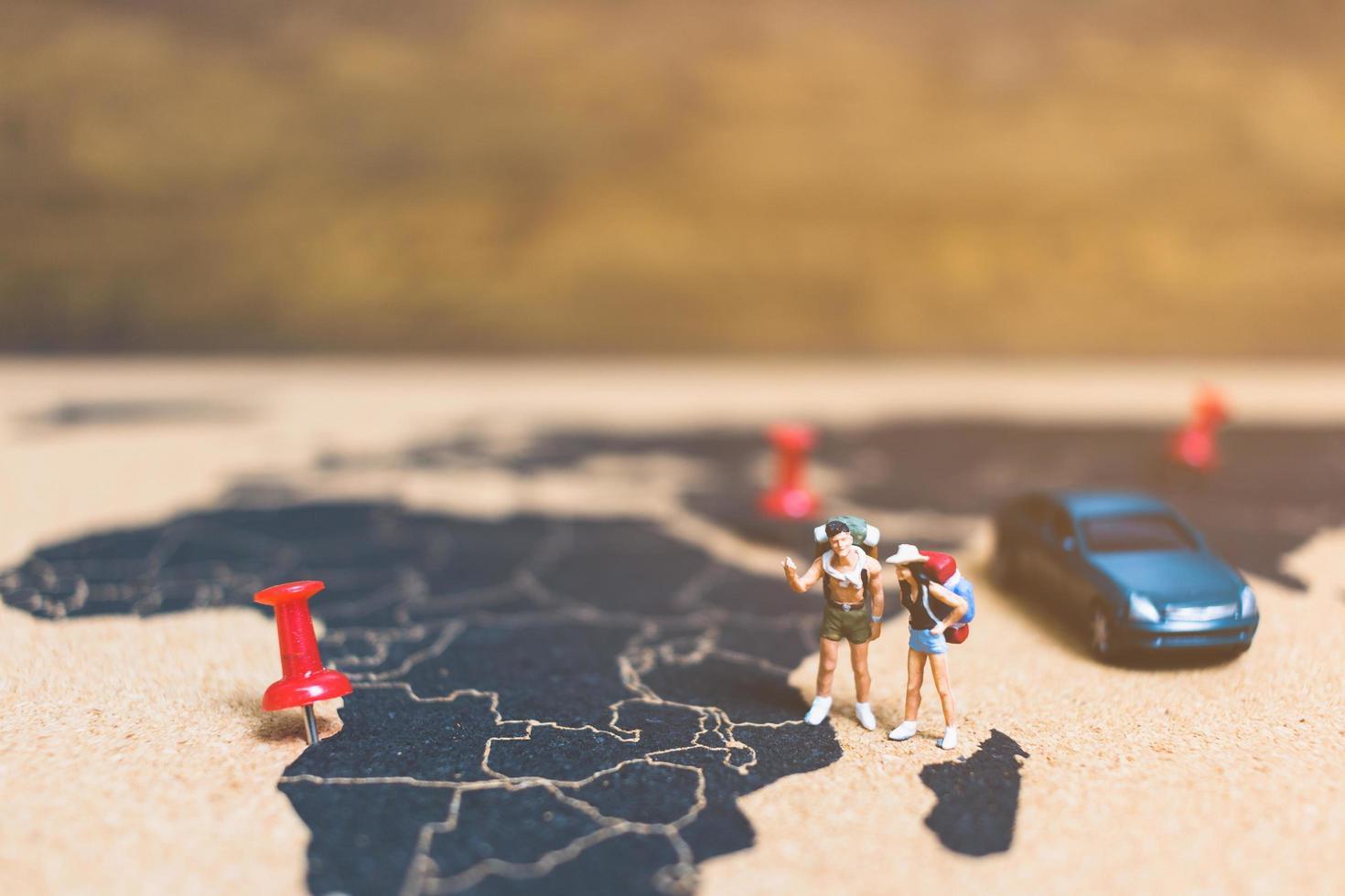miniatyrresenärer som går på en världskarta, reser och utforskar världskonceptet foto