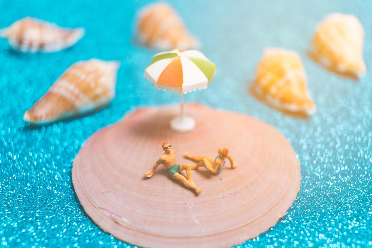 miniatyrfolk som bär baddräkter som kopplar av på ett snäckskal med glitterbakgrund foto