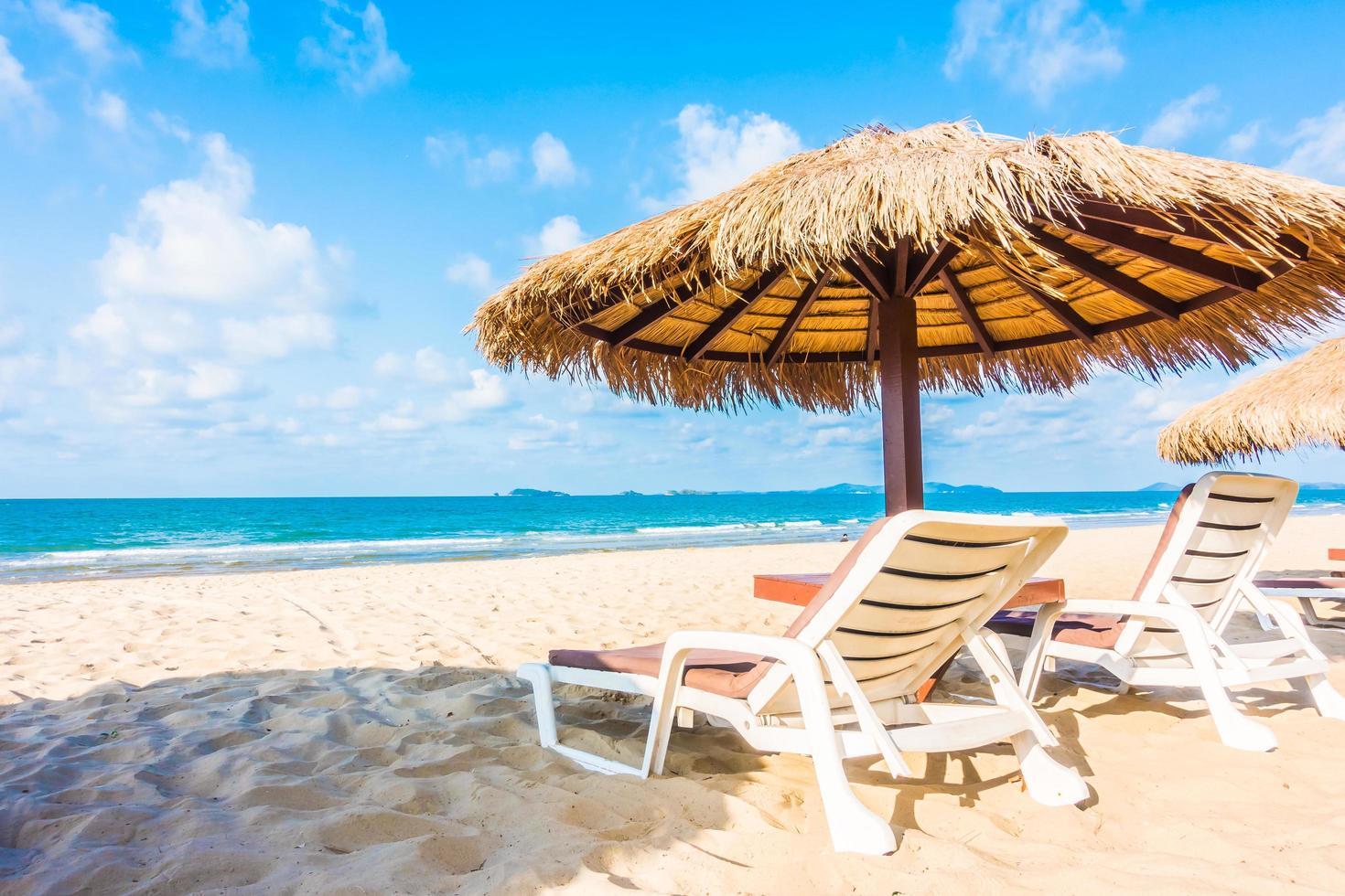 paraply och stol på den tropiska stranden foto