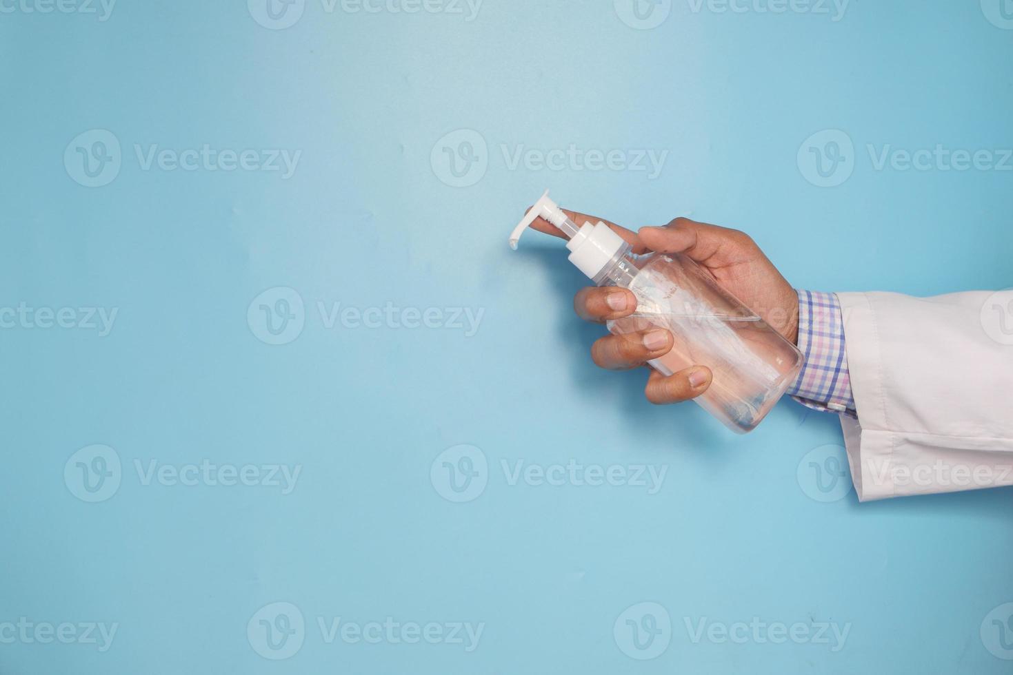läkarens hand som håller desinfektionsvätska på blå bakgrund foto