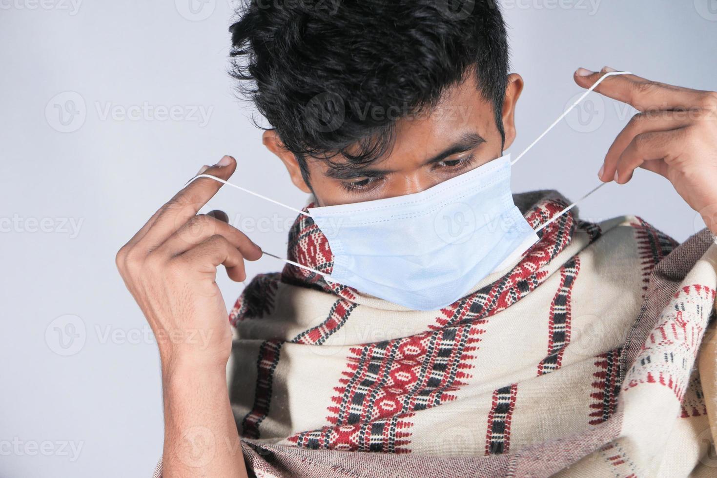ung man sätter kirurgisk ansiktsmask på foto