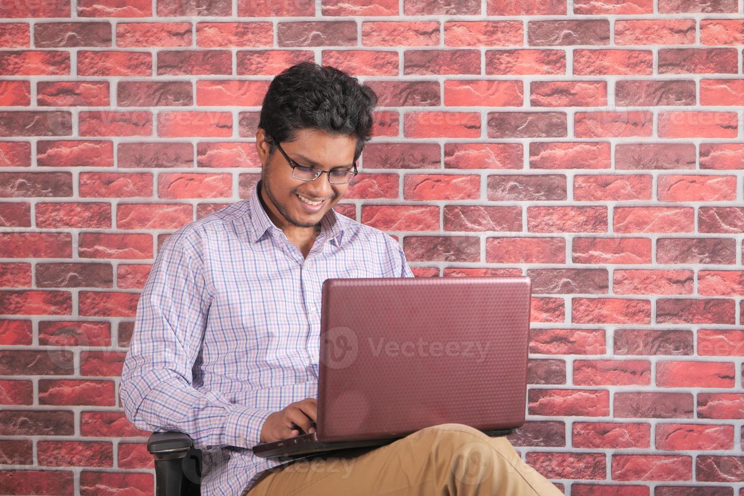 ung man som använder bärbara datorn medan han sitter i en stol foto
