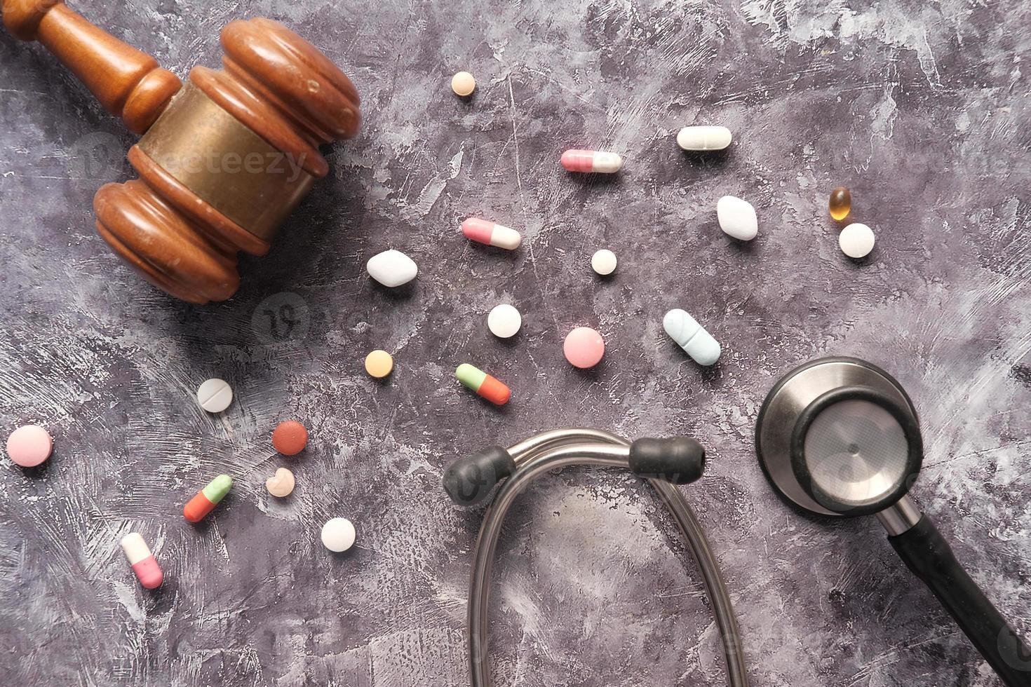 ovanifrån av ordförandeklubba, stetoskop och piller på grå bakgrund foto