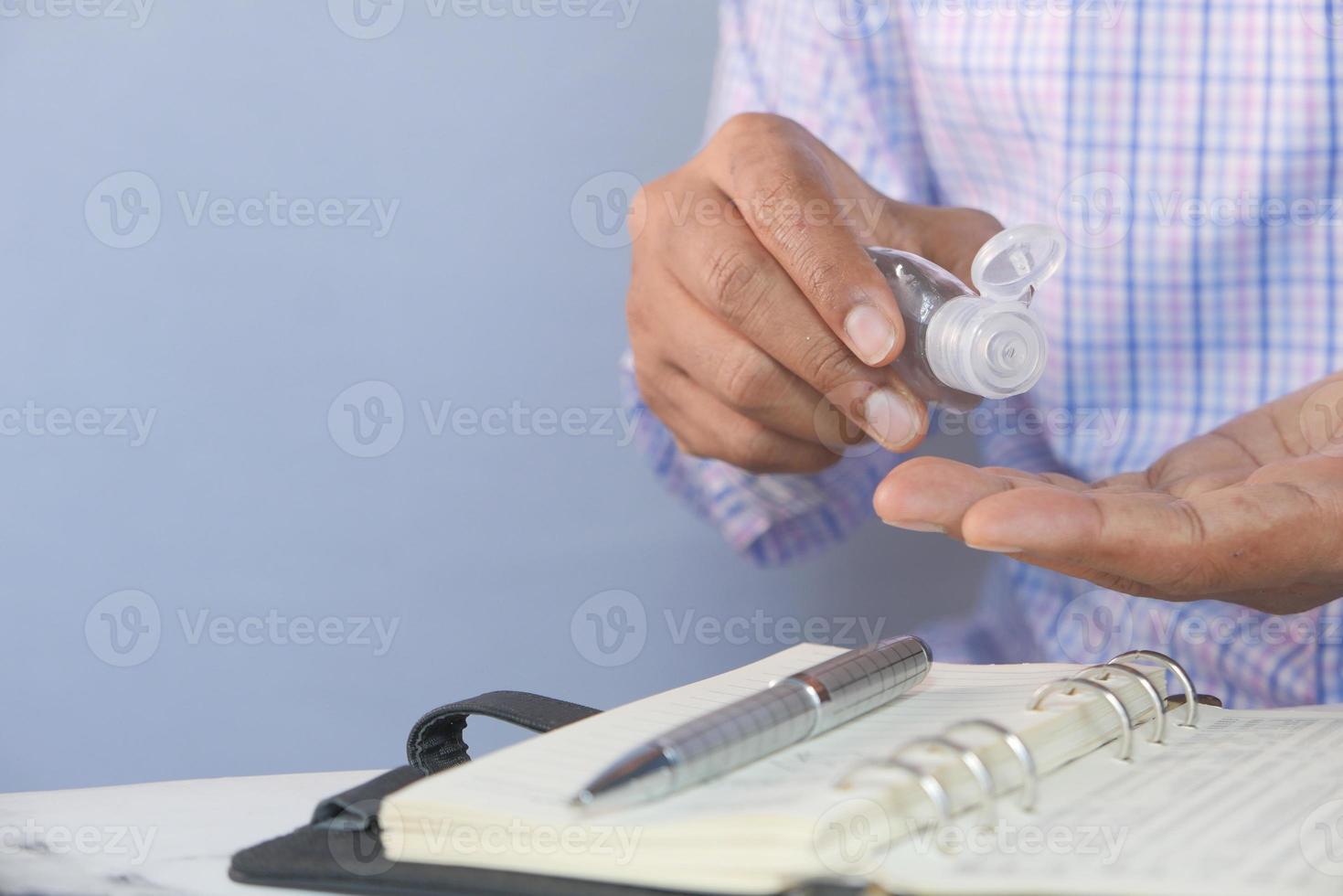 affärsman som använder desinfektionsgel på på skrivbordet foto