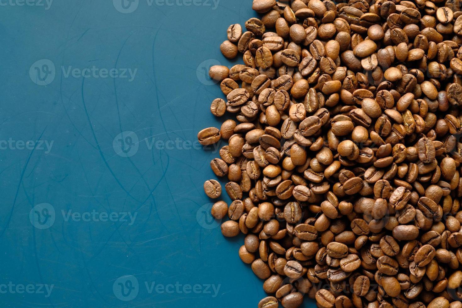 kaffebönor på blå bakgrund med kopieringsutrymme foto