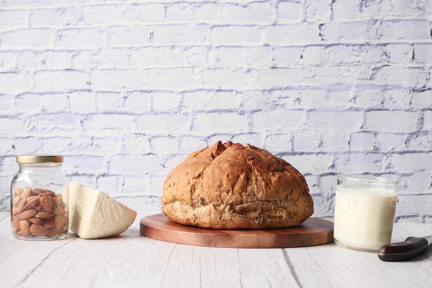 brunt bröd, ost och mjölk på neutral bakgrund foto